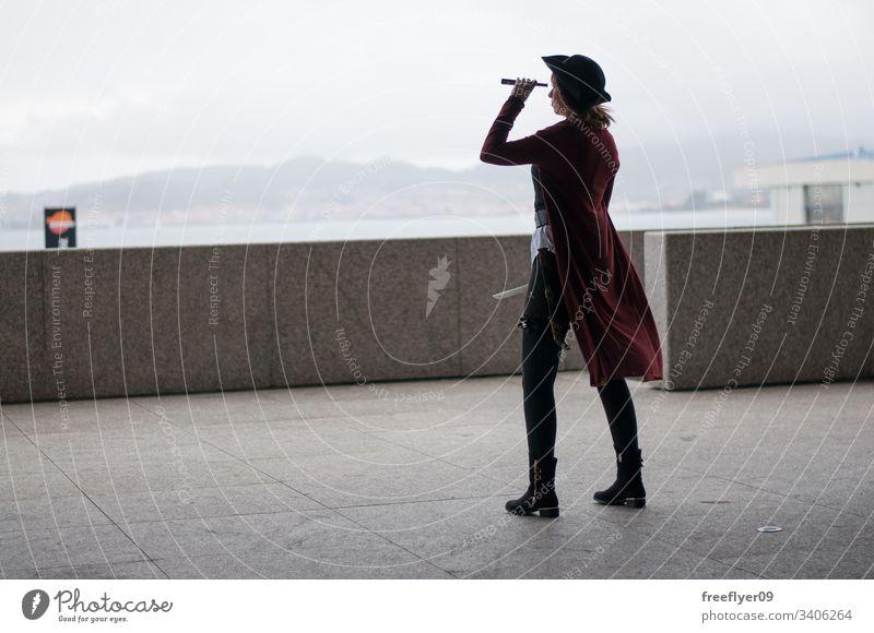 Als Piratin verkleidete Frau scannt den Horizont Frauen Verkleidung amerikanischer Ureinwohner heimatlich Amerikaner Inder Fälschung Porträt Messer Angst
