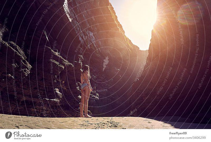 Junge Frau im Bikini, die eine Felsformation am Strand betrachtet Tourismus wandern Galicia Spanien Ribadeo Castros Illas Felsen atlantisch Bucht touristisch
