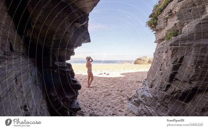 Junge Frau betrachtet eine Höhle aus Felsen in Galicien, Spanien Tourismus wandern Galicia Ribadeo Castros Illas atlantisch Bucht touristisch Kathedralen Klippe