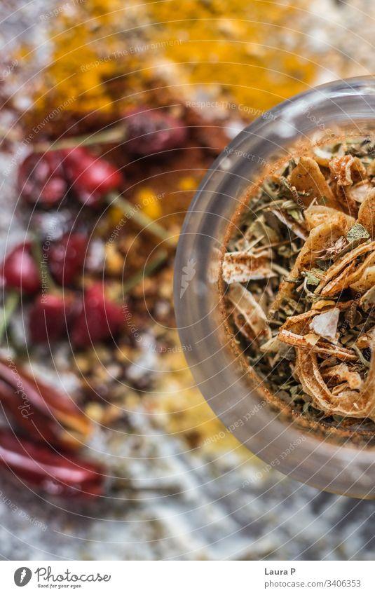 Nahaufnahme von schön arrangierten bunten Gewürzen in der Hälfte eines runden Gewürzglasgefäßes abschließen farbig farbenfroh Farben rot gelb Chili Kurkuma