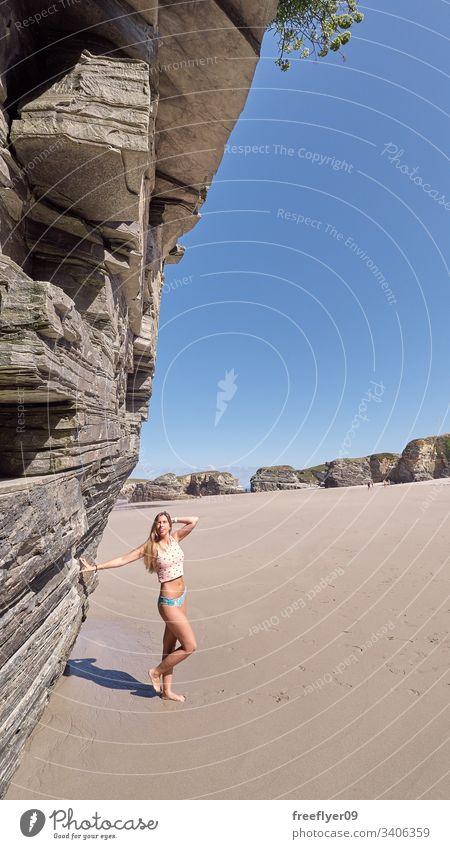Junge Frau erklimmt sich mit einer Klippe am Strand Tourismus wandern Galicia Spanien Ribadeo Castros Illas Felsen atlantisch Bucht touristisch Kathedralen Meer