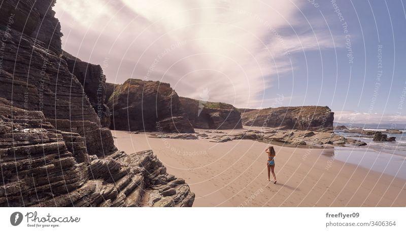 Junge Frau beim Strandspaziergang in Galicien Tourismus wandern Galicia Spanien Ribadeo Castros Illas Felsen atlantisch Bucht touristisch Kathedralen Klippe