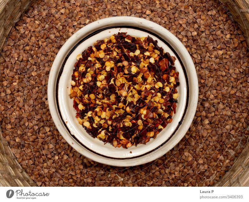 Nahaufnahme von Gewürzen in einer runden Schüssel - Chili und Buchweizen abschließen Küchenkräuter Schalen & Schüsseln rustikal lecker Lebensmittel Ernährung