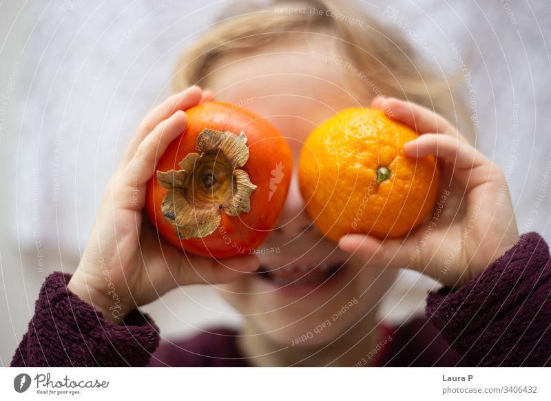 Kleines Mädchen hält eine Kiwi und eine Orange vor ihren Augen und lacht niedlich wenig Kind Spielen Spaß Lachen Lächeln Früchte orange Hände versteckend