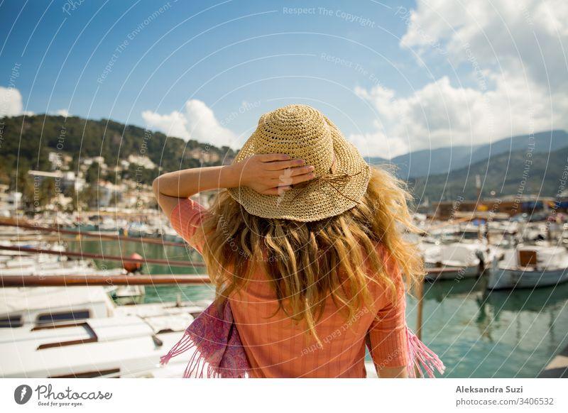 Porträt einer Frau mit leicht gelocktem Haar, Rückansicht, mit der Hand Strohhut haltend. Sonniger Hafen, Boote und Jachten, grüne Berge im Hintergrund. Das Leben genießen, glücklich reisen,