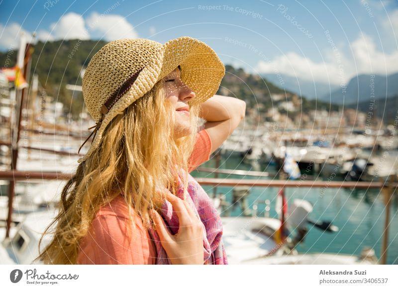 Porträt einer jungen Frau mit hellem lockigem Haar und Strohhut, die lächelnd Sonne und Wind genießt. Sonniger Hafen mit Booten und Jachten, grüne Berge im Hintergrund. Lebensfreude, fröhliche Reisende,