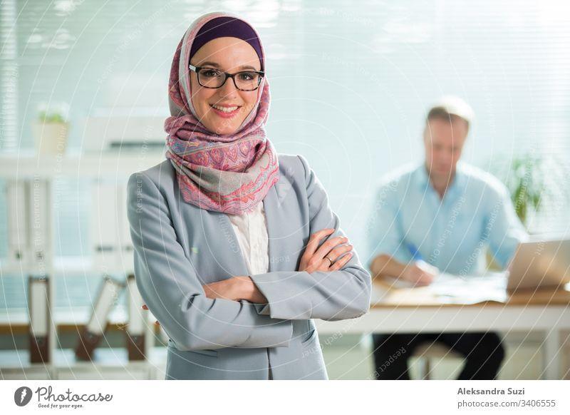 Hübsche junge Arbeiterin in Hijab, Anzug und Brille steht im Büro und lächelt. Porträt einer selbstbewussten muslimischen Geschäftsfrau. Modernes Büro mit großem Fenster, im Hintergrund ein Mann am Schreibtisch arbeitend.