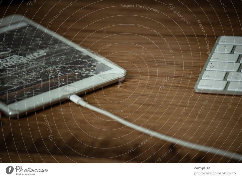 kaputter Bildschirm auf dem Schreibtisch ipad computer screen defekt glascheibe zersprungen versicherung schreibtisch arbetsplatz office büro new media hartware