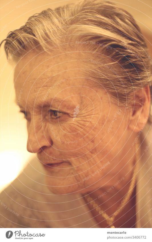 Nachdenkliche Seniorin in Zeiten von Corona Blick nach unten Porträt Unschärfe Licht Innenaufnahme Tag mehrfarbig Farbfoto Zukunft ruhig