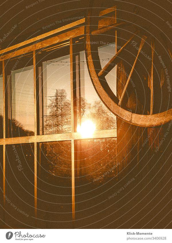 Die letzten Abend Stunden im Fenster eines Holzschuppens. *Abendsonne *Spiegelung *Fensterscheibe *Licht *Romantisch *Holz *Rad *Haus
