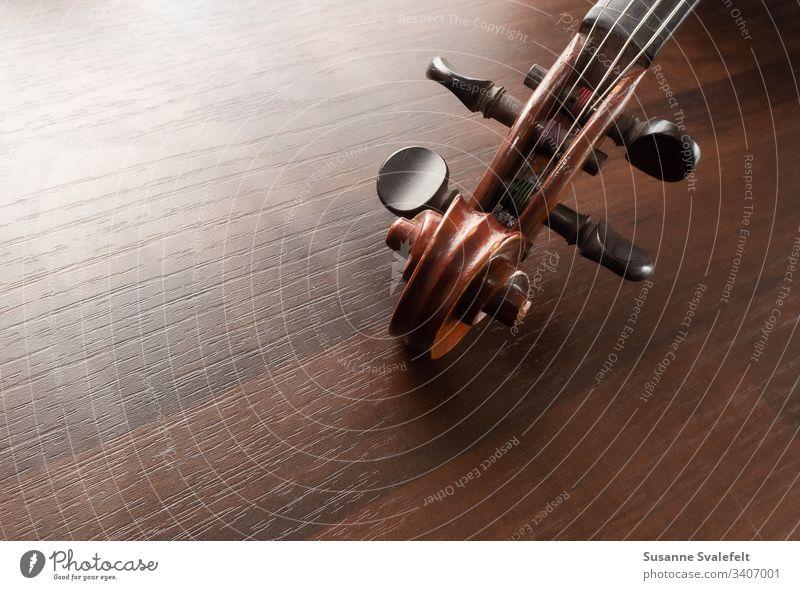 Geige oder Fiedelkopf auf dem Tisch Musik Farbfoto herumfuchteln Kopfleiste Stimmwirbel Musikinstrument Streichinstrumente Holz