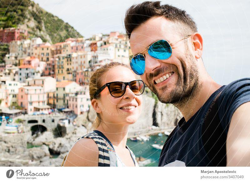 Junges Paar beim Selbstversuch in Manarola, Cinque Terre in Italien Erwachsene Freund Fotokamera Stadtbild Küste farbenfroh Europa Spaß Mädchen Freundin