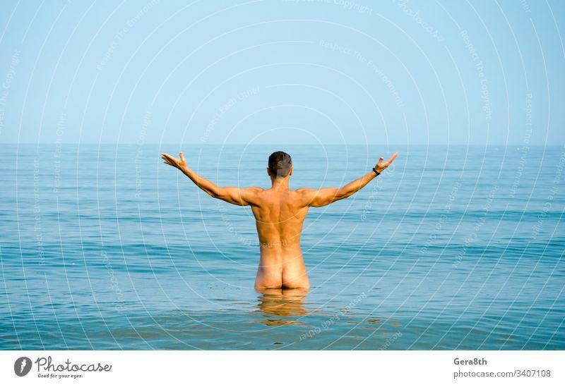 nackter Mann im blauen Wasser sportlich Rücken baden Strand Bodybuilding Verschluss Hintern Gesäß Windstille Küste Horizont Muskel nates Naturismus FKK Meer