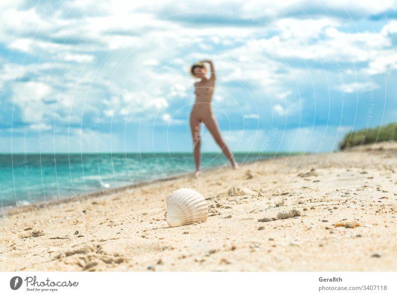 ein junges nacktes Mädchen mit Hut geht an einem leeren Strand in der Nähe der Meeresbrandung gegen den blauen Himmel mit Wolken im Sommer allein Unschärfe