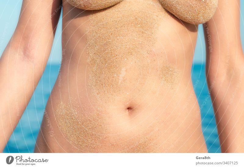 Strandsand auf einem nackten Frauenkörper auf dem Meeresgrund in Nahaufnahme Erwachsener Bauch blau Körper Frauenbrust Farbe Tag Freiheit Mädchen Sandkörner