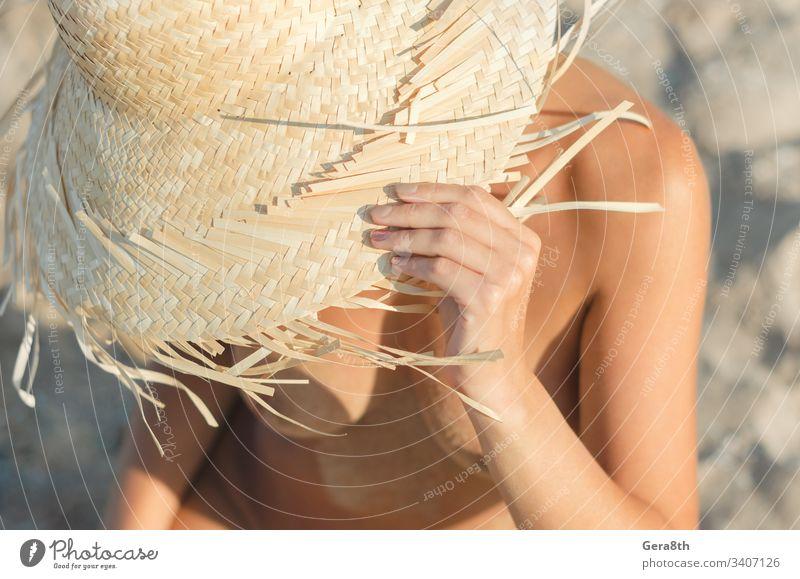 junges Mädchen mit Strohhut sitzt auf dem Sand am Strand aus nächster Nähe Körper Klima Nahaufnahme Tag Frau weiblicher Körper Finger Freiheit Hände Hut Kopf