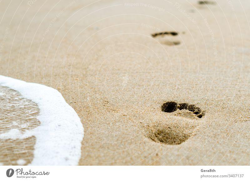 Fußabdrücke im Sand am Strand in der Nähe der Brandung Hintergrund Nahaufnahme schäumen Fußspuren Natur druckt MEER Meeresbrandung Tapete Wasser weiß gelb