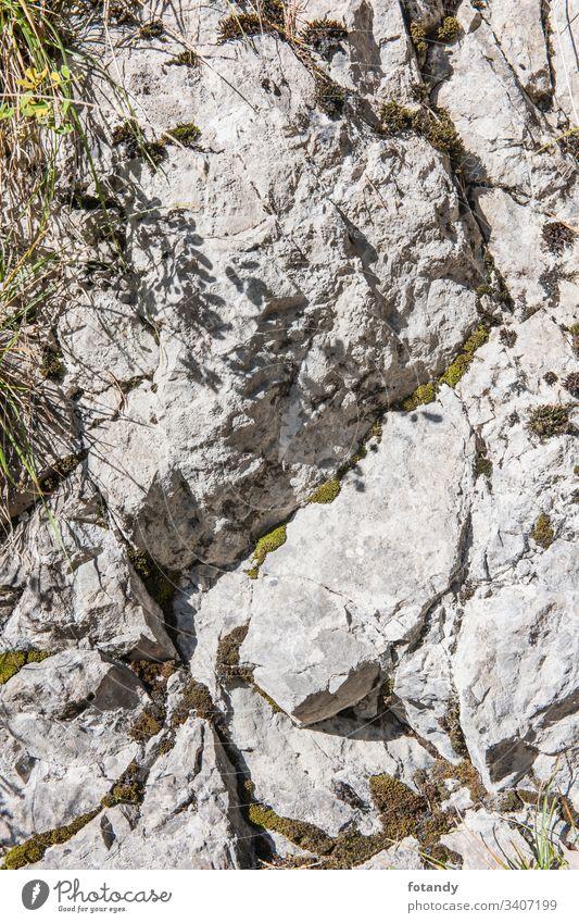 Felsen im harten seitlichen Sonnenlicht vertikal Struktur dreckig Risse Struktur-Hintergrund Felshintergrund raue Textur Tapete Wand grau Rock Stein Oberfläche