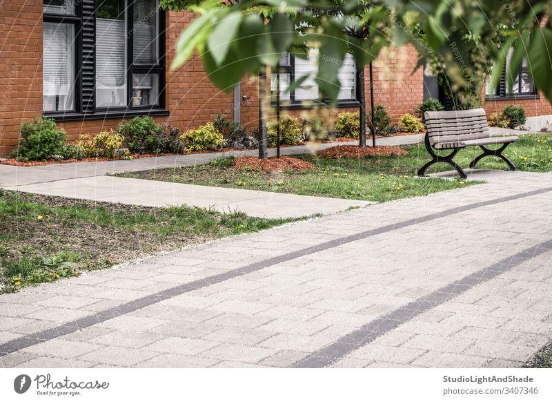 Gepflasterter Weg zu einem modernen Backsteingebäude Gebäude Haus Straßenbelag gepflastert Sauberkeit Stein Fliesen u. Kacheln Fenster Baustein Frühling Sommer