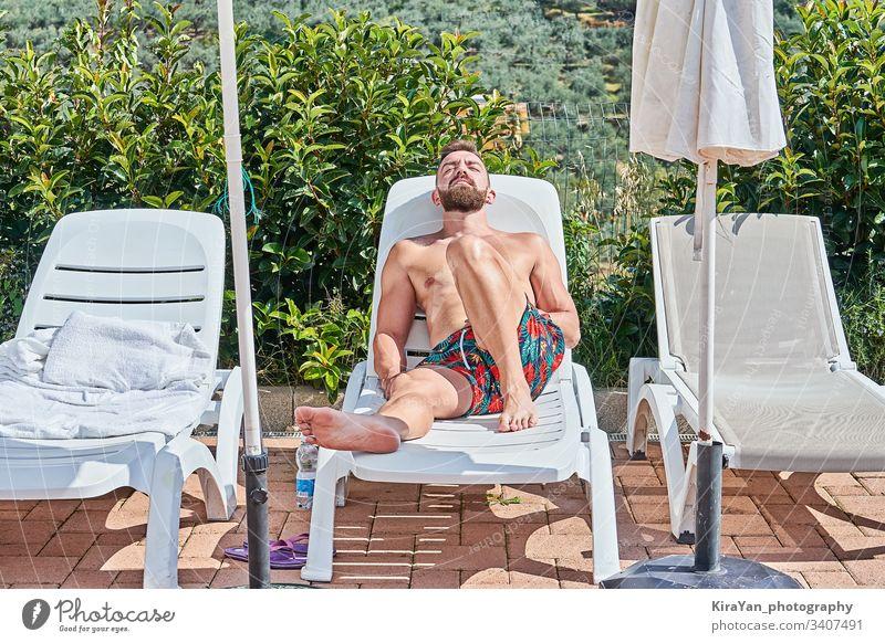 Hübscher bärtiger Mann sonnen sich auf einem Liegestuhl und genießt die Sommerzeit Freizeit Bräune männlich Person sonnig Kaukasier ruhen Erholung Pool Lügen