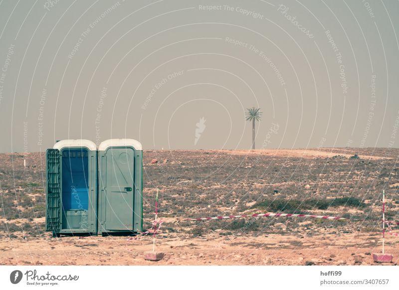 mobile Toilette in Wüste mit Flatterband und Palme Miettoilette toilettenhäuschen Sitzung 00 Plumpsklo trashig absurt Pissoir heiß ästhetisch Wärme Horizont