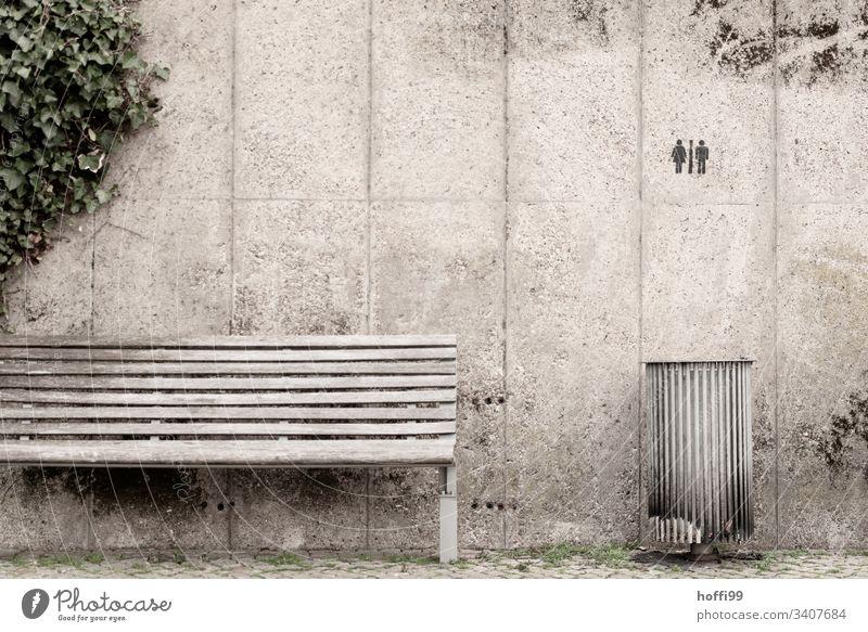 Stillleben von Bank Mülleimer mit Graffiti und Efeu Sitzbank Betonwand grau Symbol Toilette Menschenleer Mauer Tag Wand Schriftzeichen Gedeckte Farben Zeichen