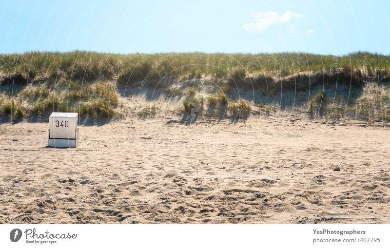 Strandlandschaft mit einem einzigen Korbstuhl im Morgenlicht allein Stuhl Küste Küstenlinie Dunes Europa Gras erwärmen Insel korb Wahrzeichen Landschaft marram