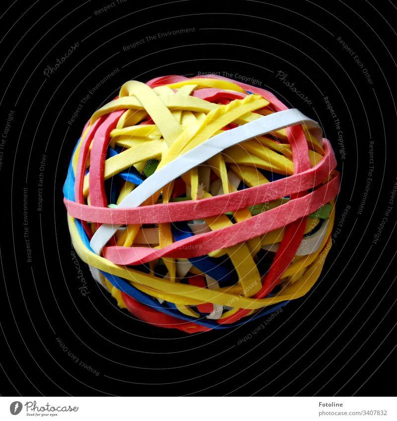 Das Objekt der Begierde - Ein Ball aus Gummibändern auf einer braunen Decke Haushaltsgummis Schwache Tiefenschärfe Farbfoto Menschenleer Nahaufnahme Kugel bunt