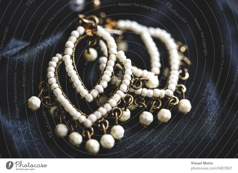 Nahaufnahme eines Paares von Ohrringen im ethnischen Stil mit weißen Perlen abstrakte Fotografie Kunst Kunst und Handwerk schön Boho Boho-Stil schick