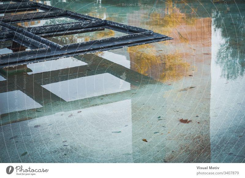 Metallische Ornamentstruktur in der Mitte eines Teiches Farbe im Freien Außenseite urban abstrakt abstrakter Hintergrund abgeblätterte Farbe rostig Architektur