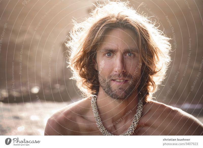 portrait - junger mann am meer lange haare entspannt sonnenuntergang strand wellen sonnenstrahlen urlaub relax huebsch lichtkranz backlight gegenlicht bart