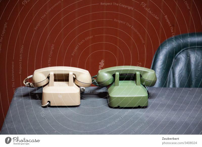 Zwei alte Telefone in beige und lindgrün auf Schreibtisch mit Ledersessel vor ochsenblutroter Wandvertäfelung Telefonhörer Sessel Lehne retro