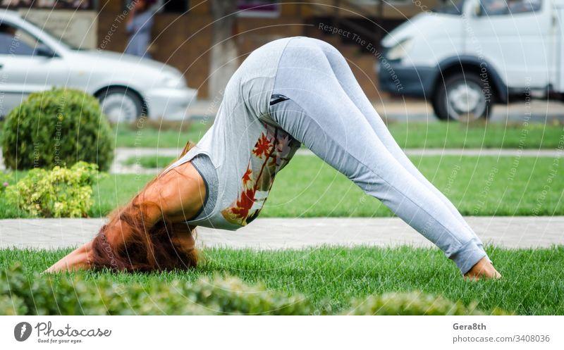junges Mädchen in Yoga-Pose auf grünem Gras auf dem Rasen auf dem Straßenhintergrund der Stadt Erwachsener hell Sträucher Autos Großstadt Stadtstraße Tag Übung