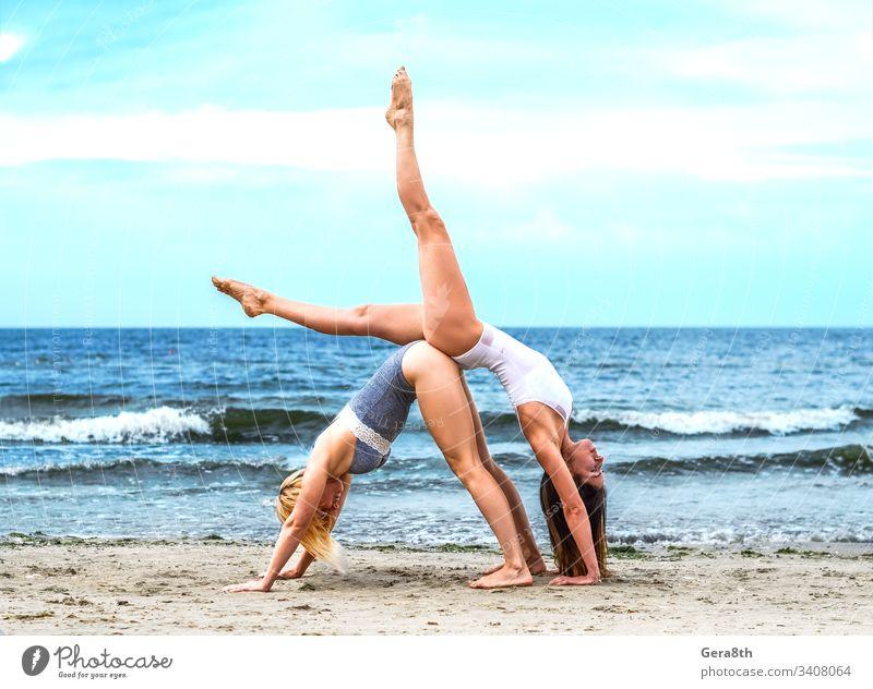 zwei junge Mädchen in weißem Oberteil und schwarzem Unterteil am Sandufer akrobatisch Akrobatisches Yoga aktiv Asana Strand blond blau Körper braunhaarig