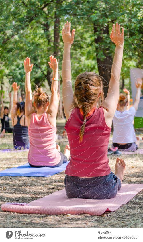 Yoga in einem Park eine Gruppe von Menschen, die auf Yogamatten sitzen und die Asana hell Windstille Klasse Farbe Veranstaltung Übung Mädchen Menschengruppe