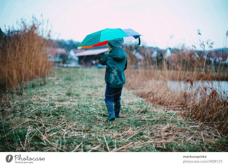 Junge mit bunten Regenschirm Wetterschutz Regenwetter Entdecker entdecken Gummistiefel