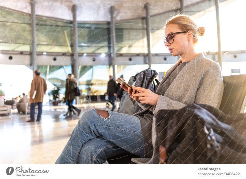 Eine weibliche Reisende, die ihr Handy benutzt, während sie an den Abfluggates im Flughafen-Terminal auf das Einsteigen in ein Flugzeug wartet. reisen Telefon