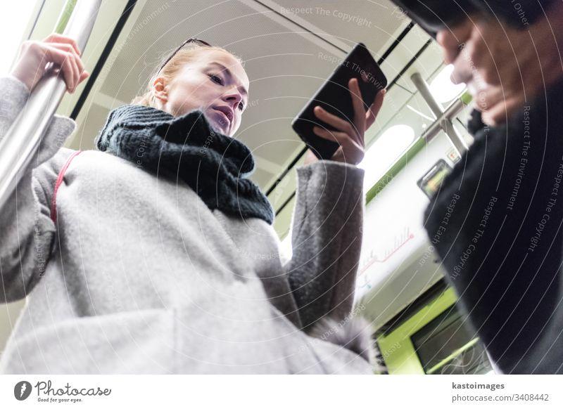 Schöne blonde Frau in Wintermantel und Schal, die während der Fahrt mit den öffentlichen Verkehrsmitteln der U-Bahn am Telefon liest. Großstadt Passagier urban