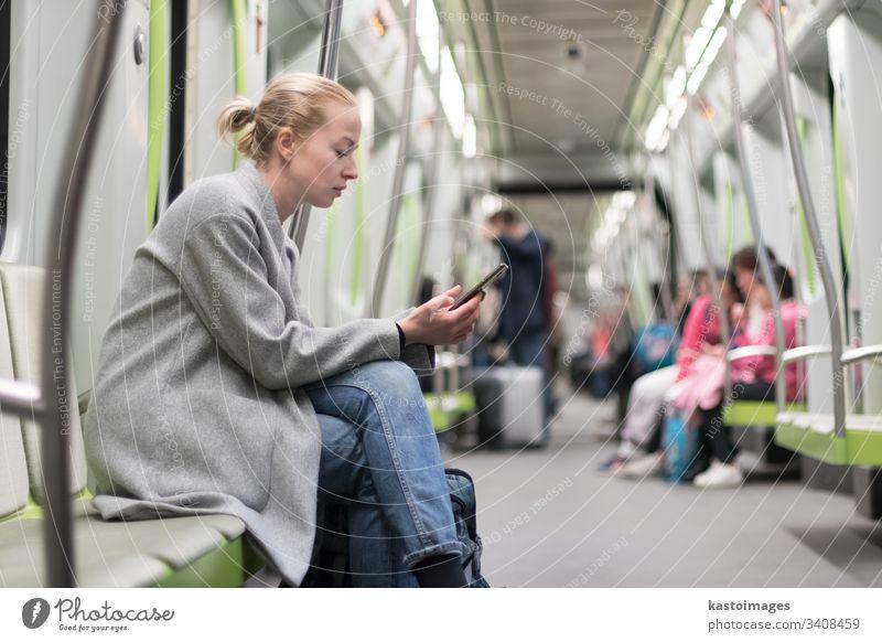 Hübsche blonde Frau im Wintermantel, die während der Fahrt mit den öffentlichen Verkehrsmitteln der U-Bahn am Telefon liest. Großstadt Passagier urban Zug