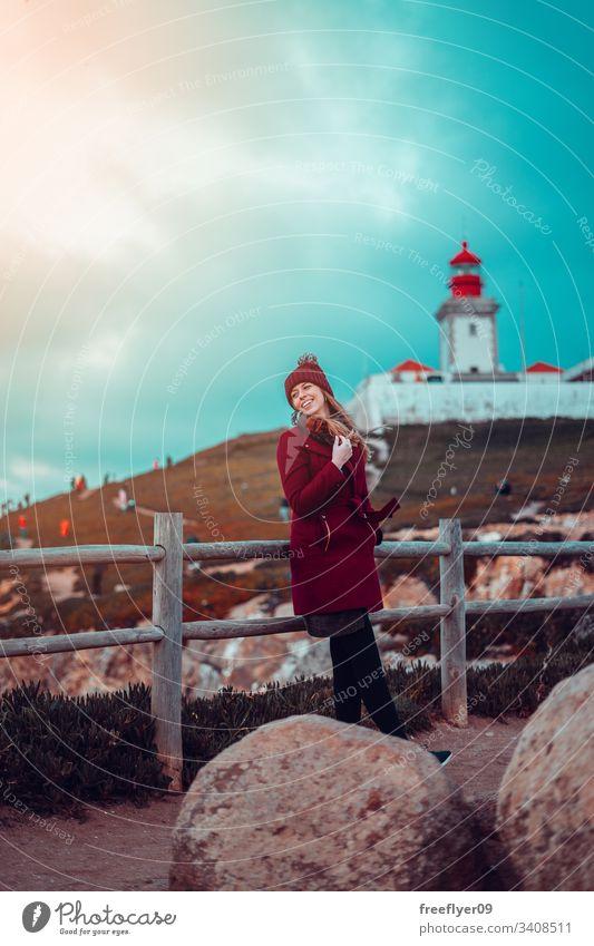 Frau steht vor dem Cabo da Roca-Leuchtturm in Sintra, Portugal eine Stehen Lachen atlantisch Wasser malerisch Wahrzeichen Saum Schifffahrt Marin Licht Klippe
