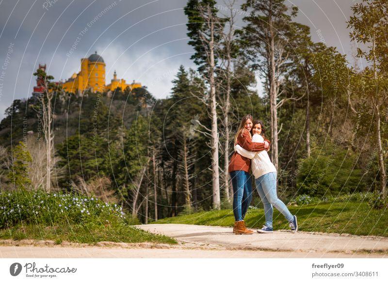 Zwei Freunde umarmen sich vor dem Pena-Palast in Sintra, Portugal Gebäude national Wahrzeichen europa Historie traditionell Baum Antiquität Berge u. Gebirge