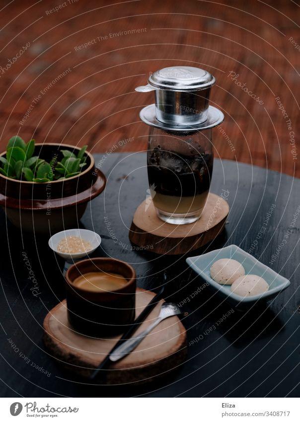 Traditioneller vietnamesischer Kaffee mit einem Tassenfilter serviert auf einem Tisch in einem Café phin Einzel-Tassen-Filter Kondensmilch Eiskaffee Espresso