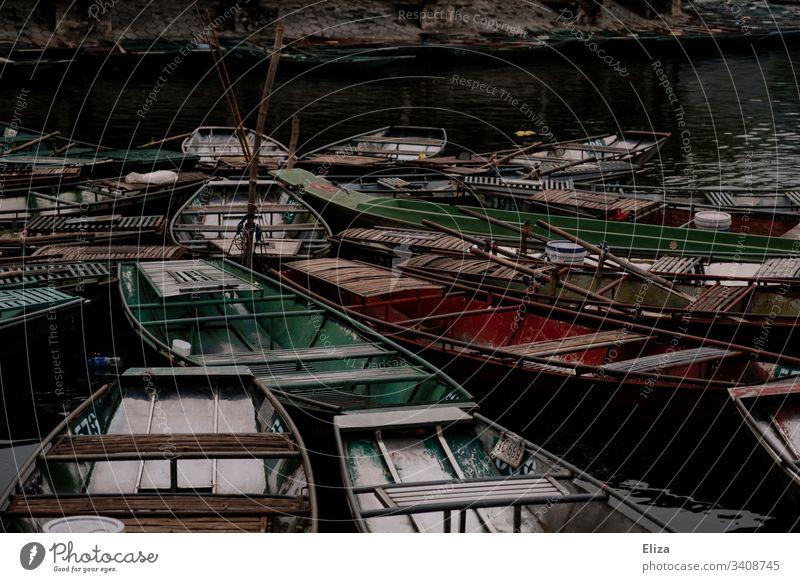 Viele bunte kleine leere Ruderboote dicht aneinander aus Holz auf dem Wasser Boote Asien Außenaufnahme Farbfoto See Ausflug Bootsfahrt Pause