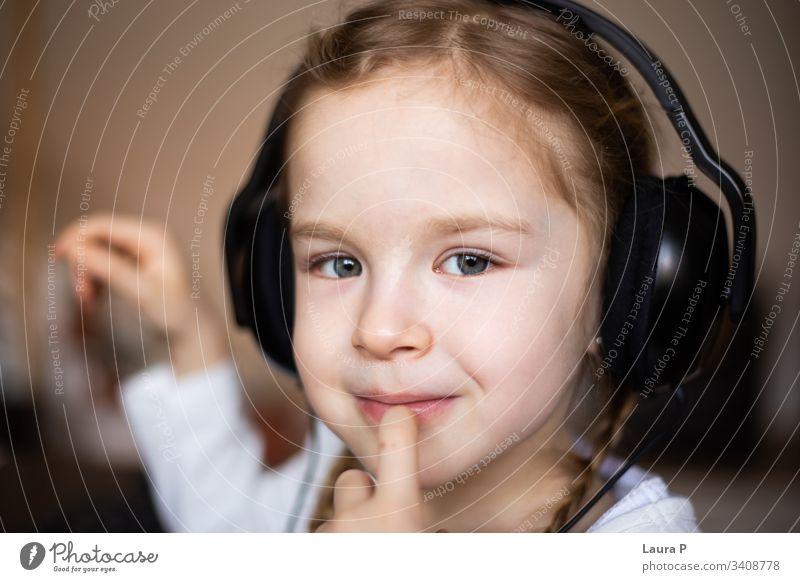 Nahaufnahme eines schönen blonden kleinen Mädchens, das über Kopfhörer Musik hört Lächeln Glück jung Schönheit Kind wenig Tochter Spaß niedlich genießen