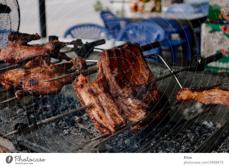 Fleisch am Spieß, das auf einem Grill brät Fleischkonsum grillen braten lecker heiß Glut Grillsaison Ernährung Grillrost Lebensmittel Grillkohle Sommer draußen