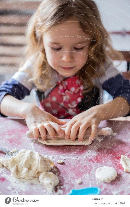 Hübsches blondes kleines Mädchen spielt mit Teig schön wenig lockig Behaarung backen Essen zubereiten Spielen Teigwaren Nudelholz abschließen Hände Süßigkeiten