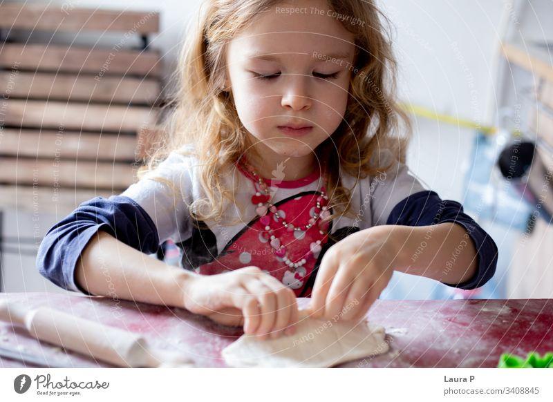 Hübsches blondes kleines Mädchen spielt mit Teig wenig schön lockig Behaarung Essen zubereiten backen Teigwaren Tisch doughtnuts Backwaren Farbfoto Mehl