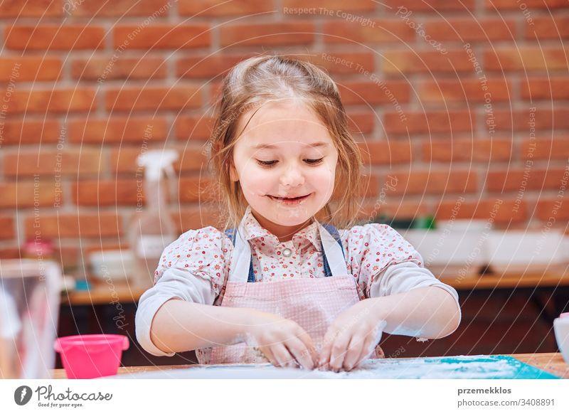 Kleines Mädchen isst den Puderzucker, der nach dem Backen von Keksen übrig bleibt. Kind nimmt am Backworkshop teil. Backkurse für Kinder, aufstrebende kleine Köche. Kochen lernen. Kombinieren und Rühren von vorbereiteten Zutaten. Echte Menschen, authentische Situationen