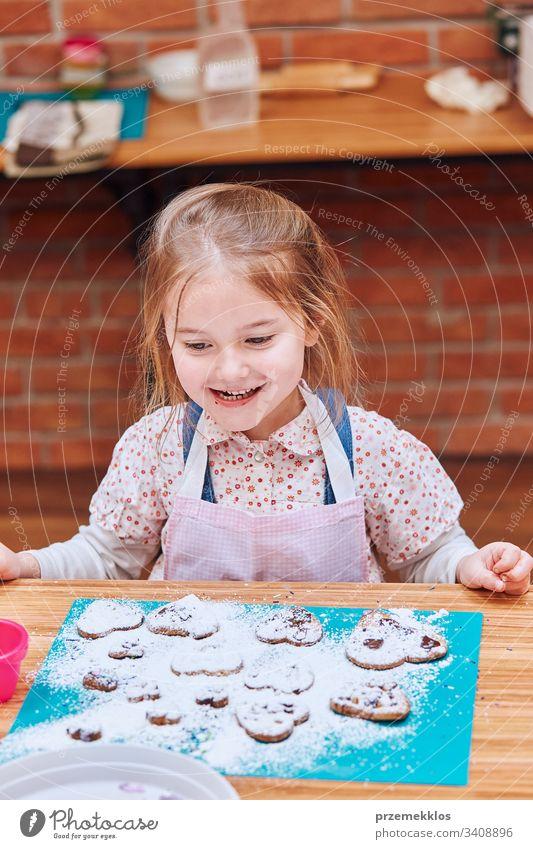 Kleines Mädchen glücklich wegen ihrer gebackenen Kekse. Kekse mit bunten Streuseln und Puderzucker dekorieren. Kind nimmt am Backworkshop teil. Backkurse für Kinder, aufstrebende kleine Köche. Kochen lernen. Kombinieren und Rühren von vorbereiteten Zutaten.