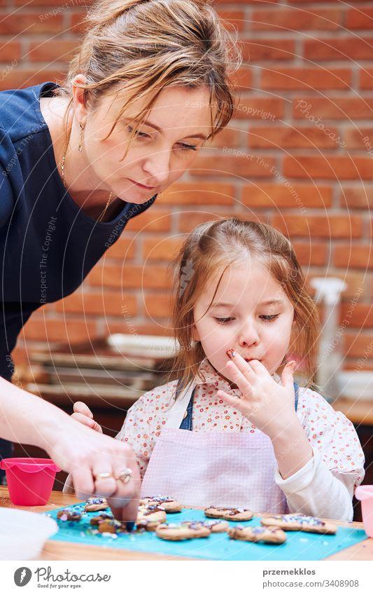 Kleines Mädchen mit Hilfe ihrer Mutter, das gebackene Kekse mit bunten Streuseln und Puderzucker verziert. Kind nimmt am Backworkshop teil. Backkurse für Kinder, aufstrebende kleine Köche. Kochen lernen. Kombinieren und Rühren von vorbereiteten Zutaten